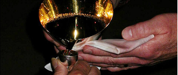 Hands pouring communion wine at Our Savior's Church